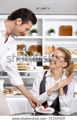 The waiter has brought to the girl a dessert in cafe - stock photo