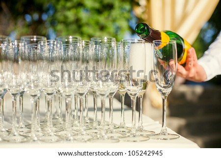 The waiter pours champagne into crystal glasses - stock photo
