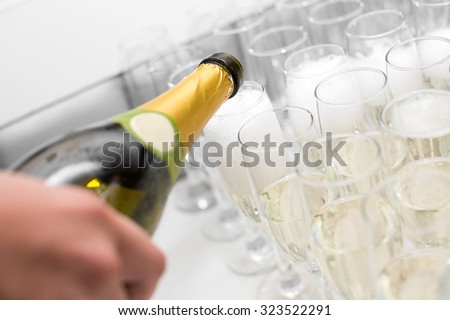 the waiter pours champagne into the glasses - stock photo