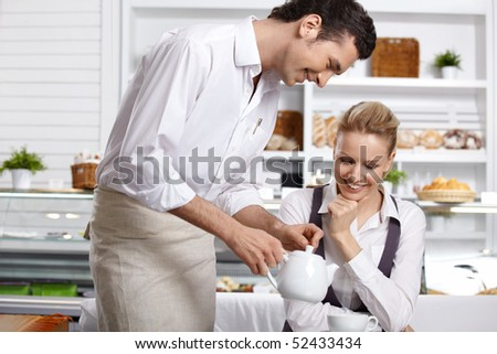 The waiter pours tea to the attractive girl in cafe - stock photo