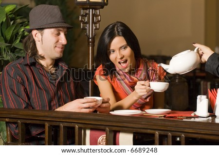 The waiter serves visitors. Behind a table at restaurant couple - the man and the woman. - stock photo