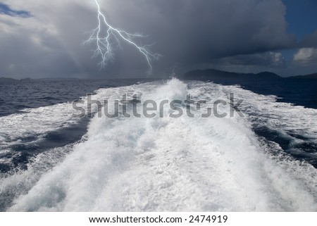 The wake from a high-speed boat as it heads away from a storm. - stock photo
