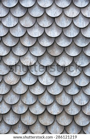 The wall covered with wooden shingles - wooden background vertical.  - stock photo