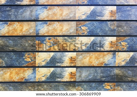The wall is fixed by rectangular stone plates with yellow blue space drawing of texture. Real nature background - stock photo