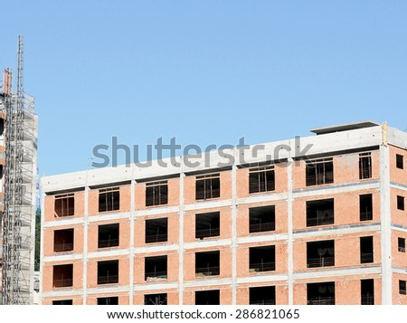 The wall of a building under construction made of red brick.