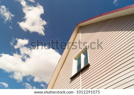 The wall of the house with a window and brown siding against the background of a blue sky with clouds.