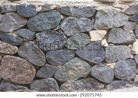 the wall of the large round stones - stock photo