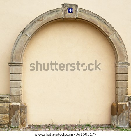 The walled-up door with stone arch with metal rusty blue table with white number four on the ancient beige plastered walls background, photo frame, place for text - stock photo