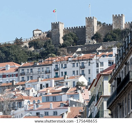 The walls of the ancient fortress over the houses of the cities of Lisbon, Portugal - stock photo