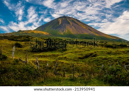 The warm coloured evening sun gracing the volcanic mount Pico on the island of Pico-Azores-Portugal - stock photo