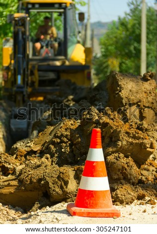 the warning road cone against a soil and the excavator digging a trench - stock photo