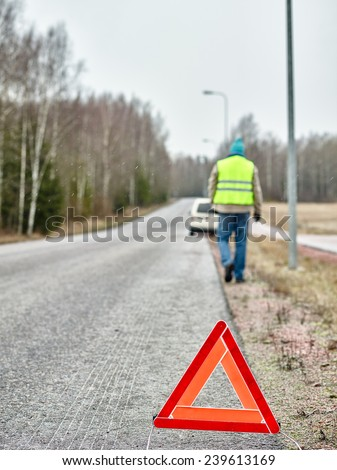 The warning triangle, mid adult man wearing reflector vest and he goes back to the his vehicle - stock photo