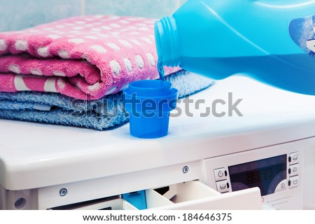 The washing machine which costs in a bathroom. The woman pours a washing-up liquid.. - stock photo