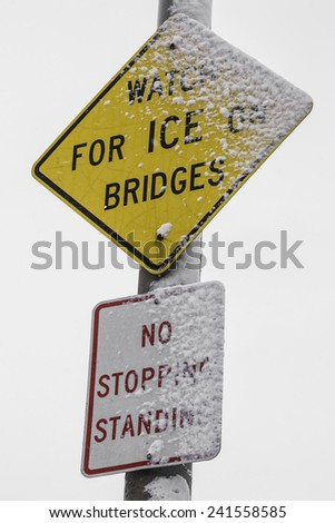 "The ""Watch for Ice on Bridges"" sign in the snow. - stock photo"