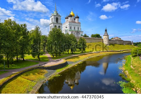 The watch tower, the walls and golden dome of Trinity Church in Pskov Kremlin reflecting in a river, Pskov, Russia