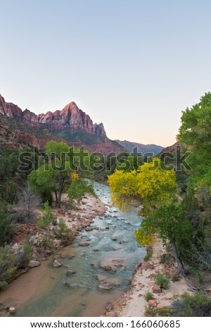 The Watchman mountain stands tall in the background over fall color and a beautiful river during the fall.   - stock photo