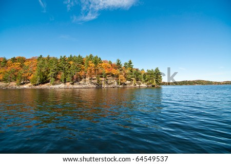 The water and shoreline of Lake of Bays in Muskoka, Ontario, Canada with colorful fall leaves and a deep blue sky.