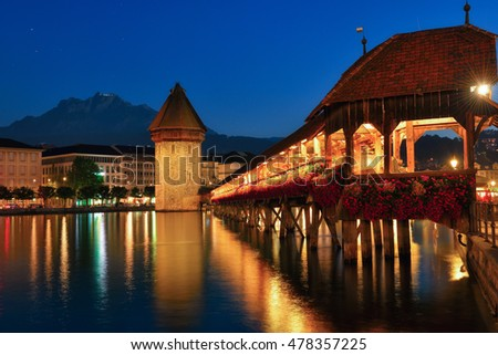 The Water Tower (Wasserturm) beside the Chapel Bridge (Kapellbrucke) in Lucerne Switzerland and backdrop is Pilatus mountain, during twilight blue hour.