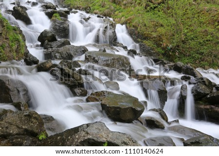 The waterfall flows along the stone ledges flowing into Lake Ritsa in Abkhazia