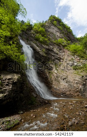 The waterfall in a mountain gorge. Summer.