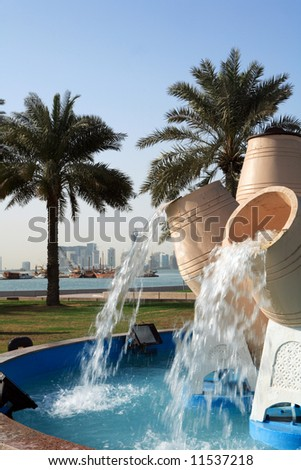 The waterpot fountains on Doha Corniche, with the Dhow Harbour, Doha Bay and the city's new high-rise commercial district in the background. - stock photo