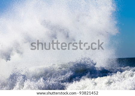 the wave is breaking on coastal rocks forming sea spray - stock photo