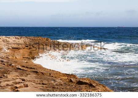 The waves beat against the rocky shore. Water flooded depressions in the rocks. Malta, Saint Julians Bay.