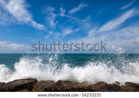 The waves breaking on a stony beach, forming a spray - stock photo