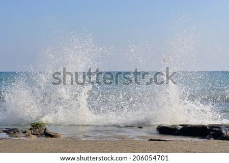 The waves breaking on stony beach, forming a spray - stock photo