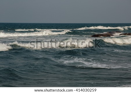 the waves near the shore foam, wave crests - stock photo