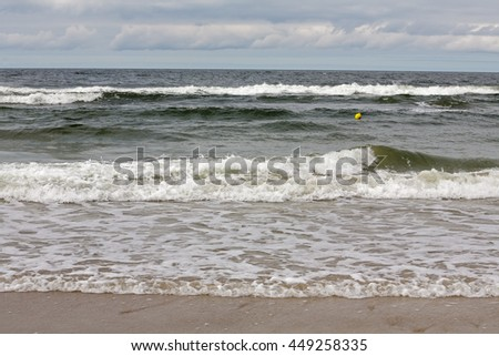 The waves of the Baltic Sea at the shore of a sandy beach in Kolobrzeg in Poland - stock photo