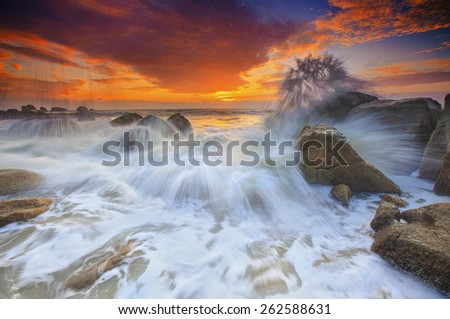 The waves splash hitting the black rocks view seascape sunrise - stock photo