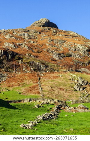The way to the pikes. A lovely view from valley fields to the imposing Langdale Pikes. - stock photo