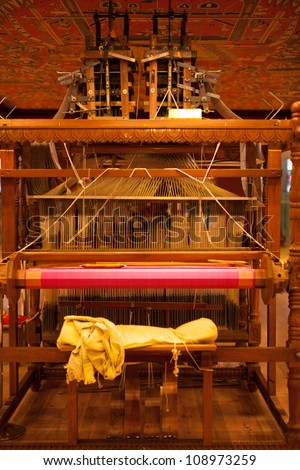 The weaver chair on the rear of a large manual wooden handloom in the process of making a pink Indian sari textile