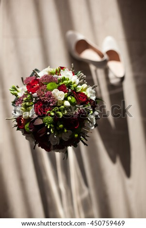 The wedding bouquet stands near shoes