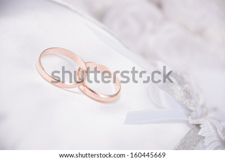The wedding invitation with wedding rings and a bouquet of the bride on a white background