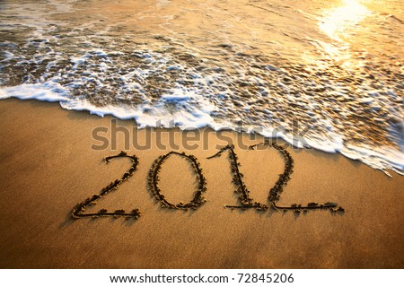 The welcome of the new year 2012 dramatic message in the sand at the beach near the ocean - stock photo