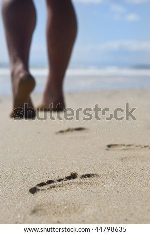 The well formed calves of a  person walking on the beach leaving behind only footprints - stock photo