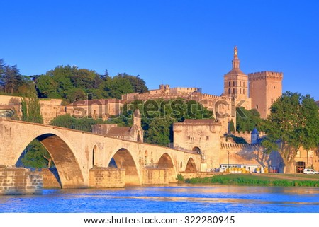 The well known bridge and distant Cathedral and Papal Palace (Palais des Papes) in Avignon at sunset, Provence, France - stock photo