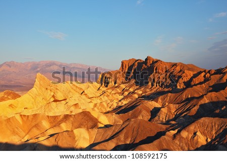 The well-known site of Death valley in California - the Zabriski-point. Picturesque hills of pink, yellow and chocolate shades on a sunset - stock photo