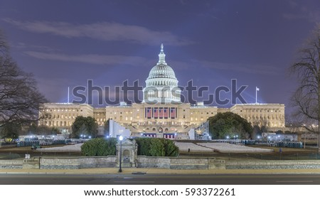 The West side of the US Capitol Building as it is prepared for the 58th presidential inauguration ceremony. The platform has been created and four of the five flags have been hung.