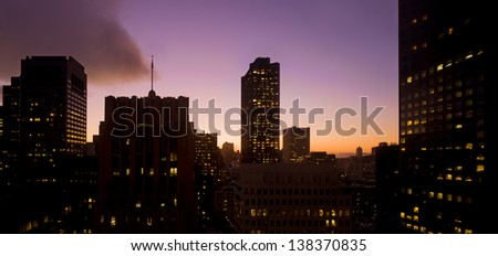 The western edge of san francisco's financial district is silhouetted against a brilliant sunset sky - stock photo