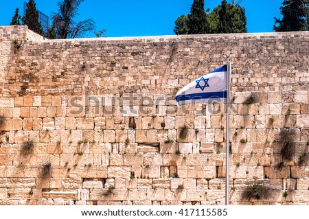 The Western wall in Jerusalem with state flag of Israel. - stock photo