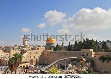 The Western Wall of the Temple and the Mosque of Omar.  The golden dome shines in the morning sun - stock photo