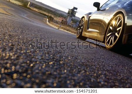 The wheels of a sport car at dusk, with the asphalt at foreground, in a racetrack. Car in a racetrack. - stock photo