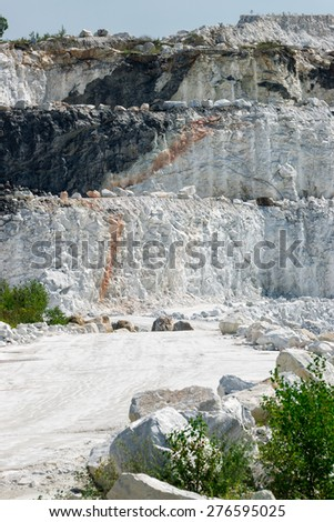 The white, chalky rock of a three tiered layered cliff at an open-pit marble mine. - stock photo