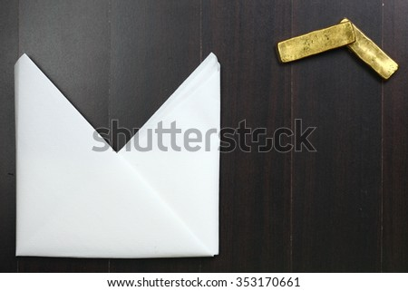 The white color paper napkin on the dark color wooden dining table floor and gold bar represent the cleaning material and business abstract concept related idea.