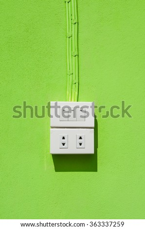 the white electric switch and plug on the green wall - stock photo