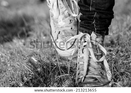 The white grunge shoes on grass. Detail of woman's legs. Black and white photography. Frozen moment of walk. - stock photo