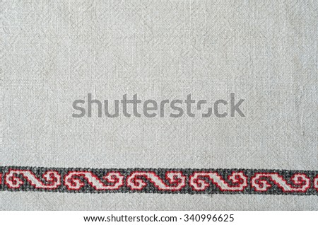 The white homespun cloth is decorated with handmade embroidery on the bottom edge. The red and black pattern is made by cross-stitch.